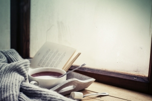 photo of tray witt hot chocolate, book and scarf on a window sill