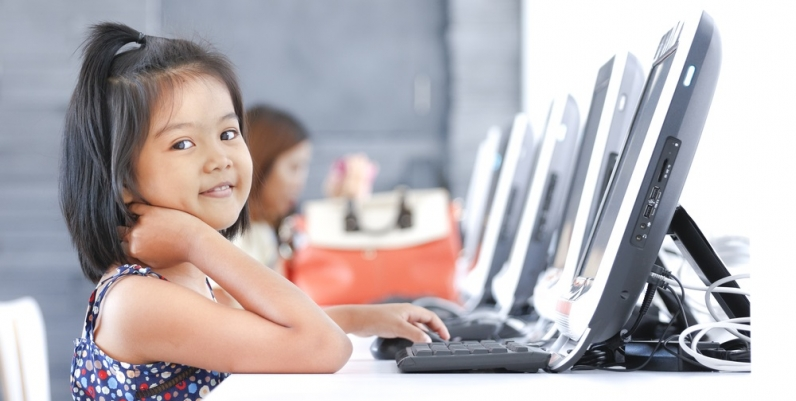 Little girl smiling in a computer lab