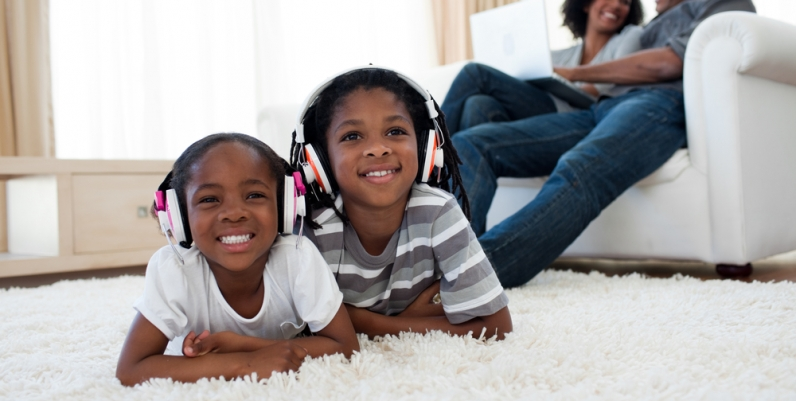 Little boy and girl lying on a carpet listening to headphones