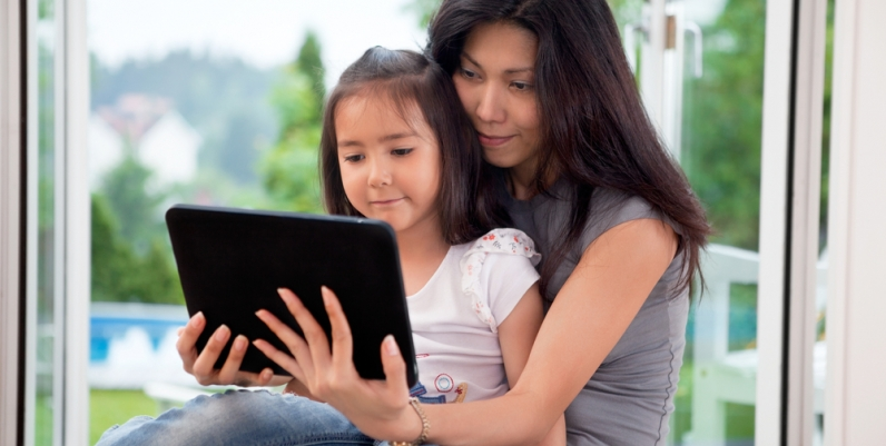 Mother and daughter reading a tablet together