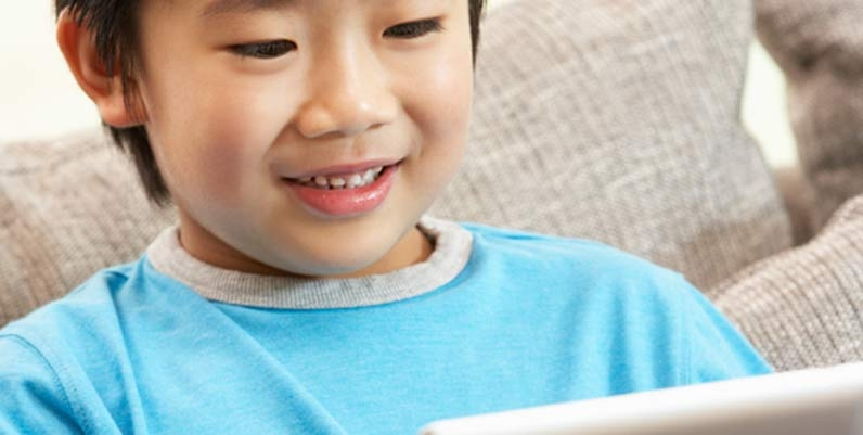 Young boy reading on a tablet computer