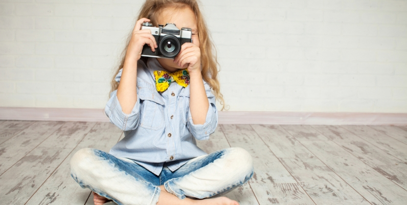 a photo of a girl with a camera sitting on the floor