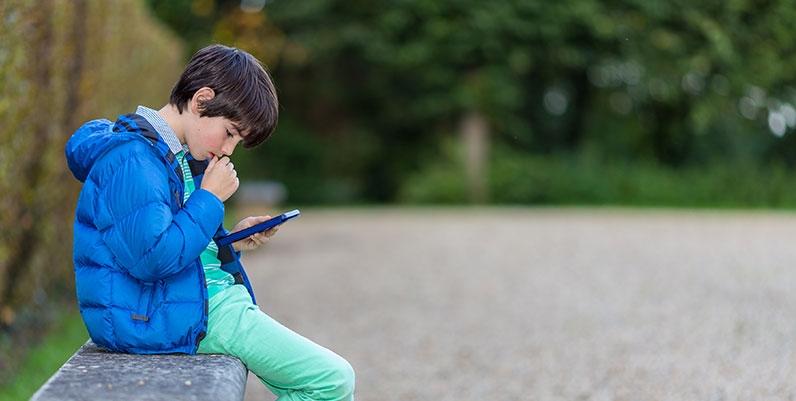 boy reading an ebook outdoors