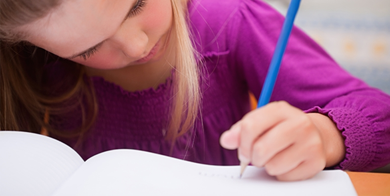 a photo of a girl writing on a notebook