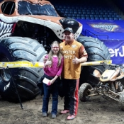 photo of girl and man in front of a Monster Truck