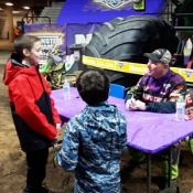 two boys talking to a monster truck driver monster truck in the background
