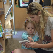 A mother and young child sitting on the floor of the HPL Bookmobile holding a music CD