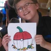 a boy holding a pumpkin colouring sheet