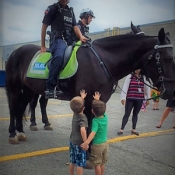 two boys speaking with a cop on a horse
