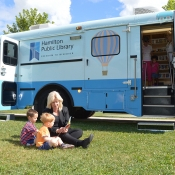Ward 13 Councillor Arlene VanderBeek reading on the grass with two young boys in front of the HPL Bookmobile