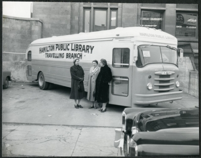 Archival photo of three women, including Chief Librarian Freda Waldon, leaning against the Hamilton Public Library Bookmobile, December 4, 1956