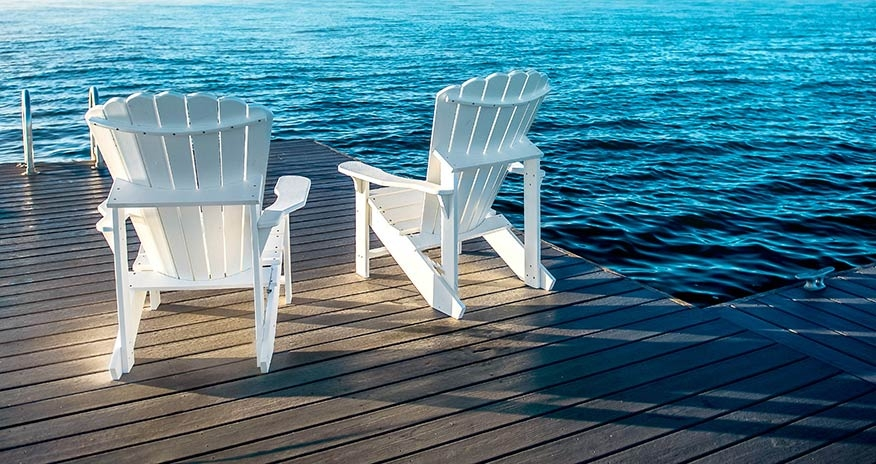 Two white Adirondack chairs sitting in front of a lake