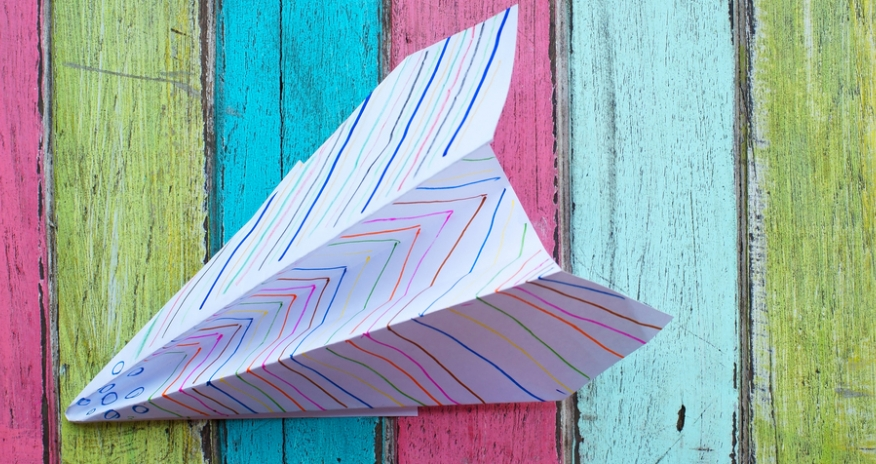 Closeup of a paper airplane on a colourful wood background