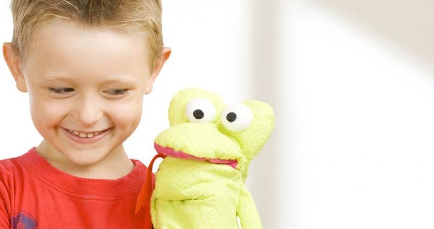 Little boy standing beside a hand puppet
