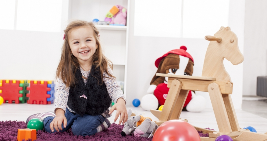 little girl sitting on the floor with toys around her