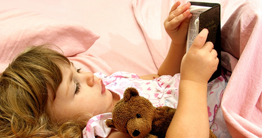 a photo of a girl reading in bed with a teddy bear